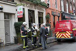 © Licensed to London News Pictures. 23/12/2014. London, UK. Firemen interview a man outside The Delhi Brasserie, an Indian restaurant in Frith Street, Westminster, London following a fire this afternoon. The fire is believed to have started in the extractor fan system in the restaurant and has now been extinguished. Photo credit : Vickie Flores/LNP