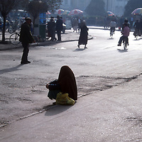 KASHGAR, 29 SEPTEMBER 2001:a veiled beggar woman sits near the mosque in Kashgar.. Uighur muslims in China's western Xinjiang province mostly stick to islamic lifestyles due to their proximity to Afghanistan & Pakistan .Today, 47 percent of Xinjiang is Uighur and 41 percent is Han. Smaller groups of other Turkic Muslims, including Kyrgyz, Kazakhs, Tajiks and Uzbeks, make up the remainder of the population ..The government maintains tight control over Uighur culture.All mosques are required to register with the government. In 2001, authorities called in 8,000 imams for special training on the Communist Party's ethnic and religious policies. In 2002, Xinjiang's top university eliminated all instruction in the Uighur language. .. . .