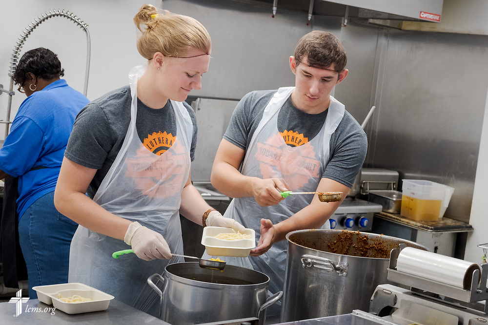 Young Adult Corps participants Courtney Haag and Hayden Duncan serve together at a meal preparation center on Wednesday, April 4, 2018, at Camp Restore in New Orleans. LCMS Communications/Erik M. Lunsford