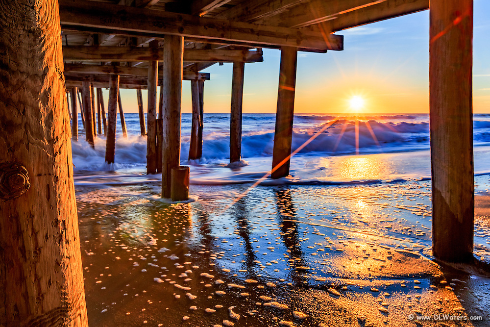 The sun peeking above horizon at Nags Head Fishing Pier Outer Banks, NC.