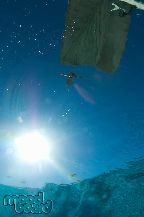 Swimmer jumping from diving board, underwater view