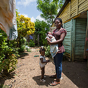 Margarita stands with two of her seven children in front of their house in the la Cubana area of San Pedro Province in the Dominican Republic, September 12, 2017. The area was not badly hit by Hurricane Irma, though it is prone to diseases, especially now in the rainy season with increased rainfall during the hurricane. Several areas with stagnant water are breeding grounds for mosquitos, increasing cases of dengue, chikungunya, zika and others.