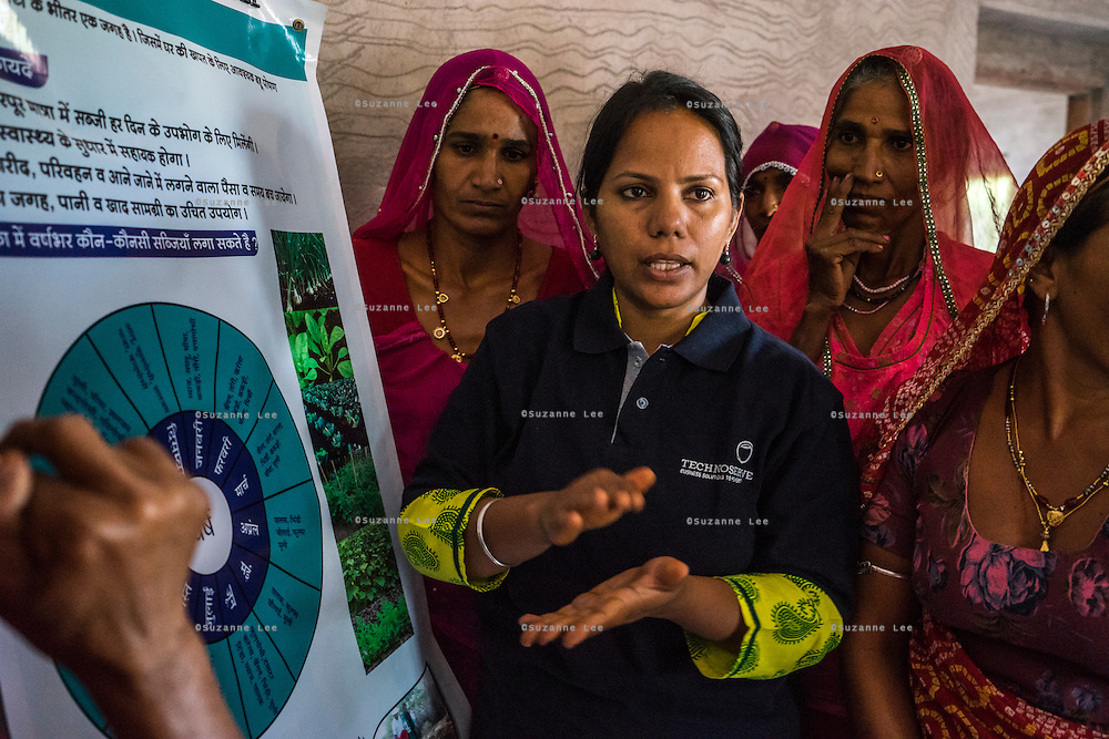 Sunayana Ingle, an associate at Technoserve, provides training to a group of women who are a part of Technoserve's kitchen garden program, in a house in Bamanwali village, Bikaner, Rajasthan, India on October 24th, 2016. Non-profit organisation Technoserve works with guar farmer's wives in Bikaner, providing technical support and training for edible gardening, to improve the nutritional quality of their food and relieve financial stress on farming communities. Photograph by Suzanne Lee for Technoserve