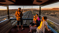 """Passengers sit out on the open air part of the observation car as the Rovos Rail train  """"Pride of Africa"""" crosses the Great Karoo Desert on it's journey between Pretoria and Cape Town, South Africa."""