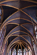 Low angle view of rib vault ceiling of the nave of the upper chapel of La Sainte-Chapelle (The Holy Chapel), 1248, Paris, France. The ribs are underlined with red strips with golden L. and the vaults are covered by golden stars. La Sainte-Chapelle was commissioned by King Louis IX of France to house his collection of Passion Relics, including the Crown of Thorns. The Sainte-Chapelle is considered among the highest achievements of the Rayonnant period of Gothic architecture. Picture by Manuel Cohen