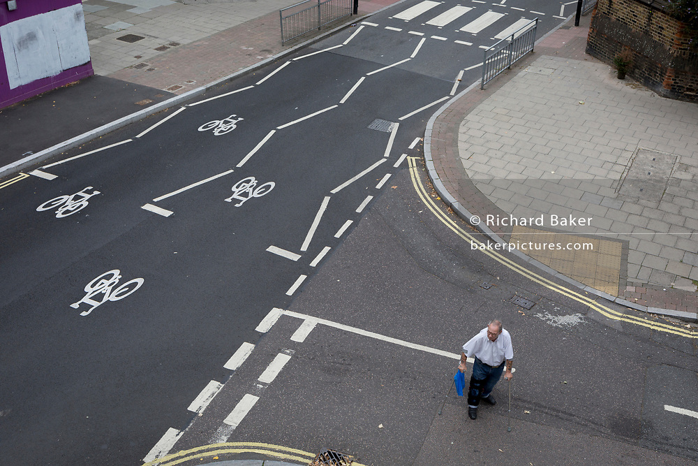 "An elderly man struggles to cross the road near the soon-to-be demolished Aylesbury Estate, on 4th September 2018, in Southwark, London, England. The Aylesbury Estate contained 2,704 dwellings in approximately 7500 residents and built between 1963 and 1977. There were major problems with the physical buildings on the estate and the poor perception of estates in Britain as a whole have led to the Aylesbury Estate gaining the title of ""one of the most notorious estates in the United Kingdom."