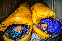 Two female mountaineers warm up in down-insulated bags on a cold winter night in Mont Blanc Massif.