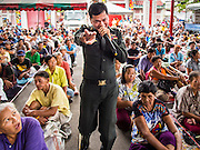 """09 AUGUST 2014 - BANGKOK, THAILAND:   A policeman sings karaoke to keep people entertained at the Ruby Goddess Shrine in the Dusit section of Bangkok. The seventh month of the Chinese Lunar calendar is called """"Ghost Month"""" during which ghosts and spirits, including those of the deceased ancestors, come out from the lower realm. It is common for Chinese people to make merit during the month by burning """"hell money"""" and presenting food to the ghosts. At Chinese temples in Thailand, it is also customary to give food to the poorer people in the community.        PHOTO BY JACK KURTZ"""