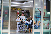 """30 NOVEMBER 2012 - BANGKOK, THAILAND: Volunteer medics with the Ruamkatanyu Foundation check a woman who collapsed on a Bangkok street into Police General Hospital during a Friday night shift. The Ruamkatanyu Foundation was started more than 60 years ago as a charitable organisation that collected the dead and transported them to the nearest facility. Crews sometimes found that the person they had been called to collect wasn't dead, and they were called upon to provide emergency medical care. That's how the foundation medical and rescue service was started. The foundation has 7,000 volunteers nationwide and along with the larger Poh Teck Tung Foundation, is one of the two largest rescue services in the country. The volunteer crews were once dubbed Bangkok's """"Body Snatchers"""" but they do much more than that now.    PHOTO BY JACK KURTZ"""