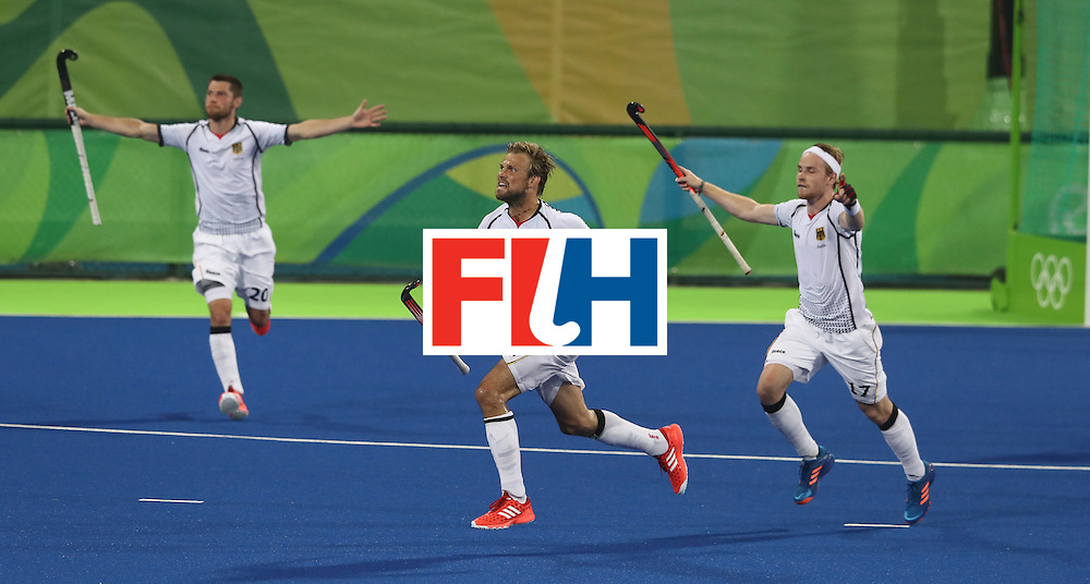 RIO DE JANEIRO, BRAZIL - AUGUST 14:  Moritz Furste, (C) of Germany who scored a late equalising goal celebrates with team mates Christopher Ruhr (R) and Martin Zwicker (L) during the Men's hockey quarter final match between the Germany and New Zealand on Day 9 of the Rio 2016 Olympic Games at the Olympic Hockey Centre on August 14, 2016 in Rio de Janeiro, Brazil.  (Photo by David Rogers/Getty Images)