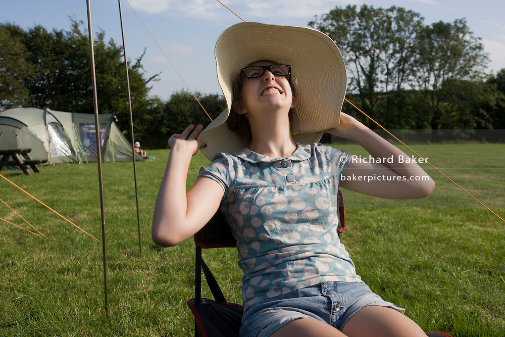 A 15 year-old teenage girl is happy in a field whilst on a family camping holiday.