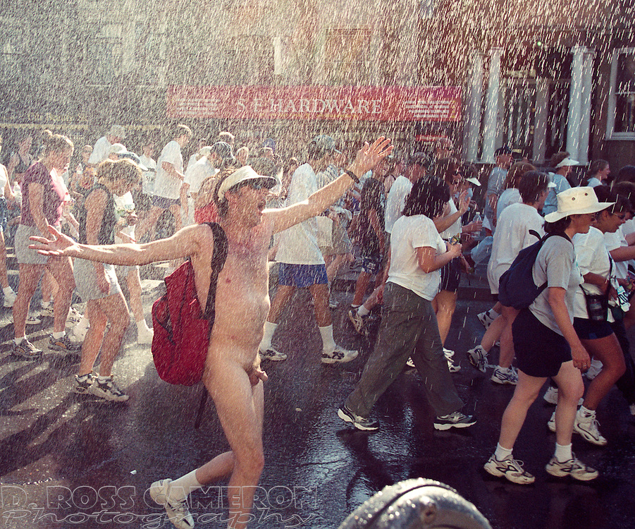 An unidentified naked man exults at a spray of cooling water while moving along Fell Street at the 89th running of the Bay to Breakers 12K race, Sunday, May 21, 2000 in San Francisco. (Photo by D. Ross Cameron)
