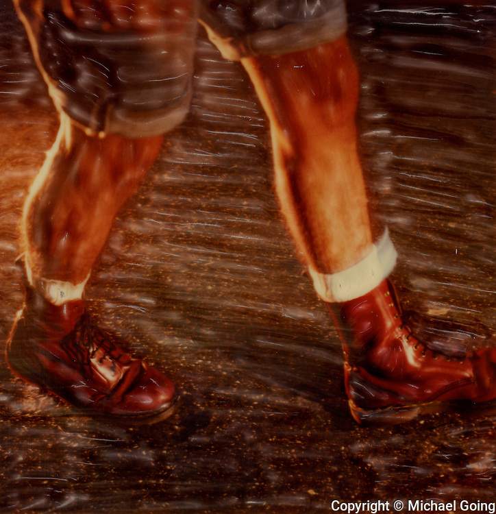 altered Polaroid SX-70 photograph of man walking wearing Doc Martens close up