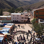 Villagers dance in the streets of Macha during the Tinku Festival. Macha, Bolivia, 4th May 2010, Photo Tim Clayton ..Each May, up to 3000 thousands indigenous Bolivian indians descend on the isolated mountainous village of Macha 75 miles north of Potosi in the Bolivian Andes. The 600 year old pre-hispanic Bolivia Festival of Tinku sees villagers from all over the region march into town to be pitted against each other in a toe to toe fist to fist combat.. They dance and sing in traditional costume and drink 96% proof alcohol along with chicha, a fermented beverage made from corn. Townspeople and sometimes the police oversee proceedings who often use tear gas to try and control the villages, whipped into a fighting frenzy by the dancing and alcohol, but as the fiesta goes on things often escalate beyond their control, with pitched battles between rival villages break out,  The blood spilt is an offering to the earth goddess - Pachamama - to ensure a good harvest for the coming year. Over the years dozens have died, yet the rite continues.