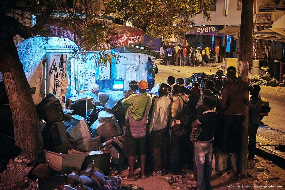 On two sides of a street in Dakar, groups are watching the wrestling match on television at the Senegalese Independence Day on April 4. The Senegalese people celebrate Independence Day traditionally with some major wrestling fights. Almost the entire population in Senegal, from small children to old women, follow the wrestling matches on TV or, if possible, at the stadium.