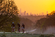 UNITED KINGDOM, London: 18 April 2018 Cyclists cycle in front of the London city skyline this morning in Richmond Park. Londoners will be enjoying the weather today as temperatures are set to reach a high of 25 degrees Celsius in the capital. Rick Findler / Story Picture Agency
