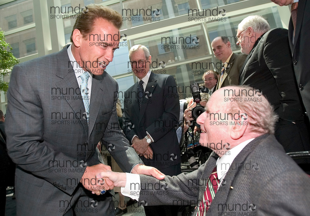 Toronto, Ontario ---30/05/07--- Governor of California Arnold Schwarzenegger shakes hands with Dr. Ernest McCulloch, who is credited with creating the first  method to identify stem cells in 1963, following an announcement of collaboration with the government of Ontario on Stem cell research at MaRS Discovery District in Toronto May 30, 2007..GEOFF ROBINS AFP