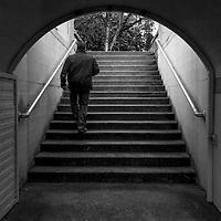 Man walking through dark passge and up a flight of stairs.