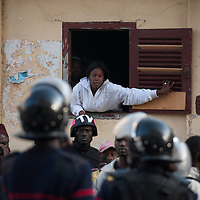 A woman talks to the police force in central Dakar, Senegal Friday, Feb. 17, 2012..Anti-government protesters and police clashed for a third consecutive day Friday, engaging in running street battles of rock throwing and tear gas in the streets of Dakar's downtown Plateau neighborhood. Demonstrators are defying a government ban on protests to call for the departure of 85-year-old President Abdoulaye Wade, who is running for a third term in next week's election..COPYRIGHT:Sylvain Cherkaoui