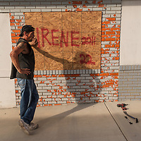 "Ray Nichols takes a break from hanging a plywood sheet that reads ""IRENE 2011"" over the windows of Beach Bumz bar in Carolina Beach, N.C., Wednesday, October 5, 2016. Southeaster North Carolina is preparing for the possible effects of Hurricane Matthew. Photo by Michael Cline Photography"