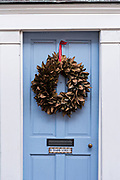 A blue wooden door of a historic home decorated with a Magnolia leaf Christmas wreath at 0 Tradd Street in Charleston, SC.