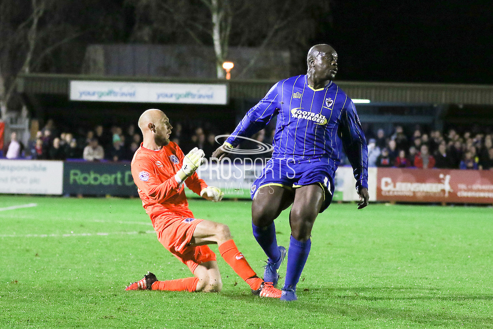 Mark Cousins (goalkeeper) of Dagenham & Redbridge beats Bayo Akinfenwa of AFC Wimbledon to the ball during the Sky Bet League 2 match between AFC Wimbledon and Dagenham and Redbridge at the Cherry Red Records Stadium, Kingston, England on 24 November 2015. Photo by Stuart Butcher.