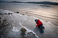 JEROME A. POLLOS/Press..Theo Behrmann, 6, slides across the ice Monday on the shoreline of Lake Coeur d'Alene during an afternoon walk with his mother and sister.