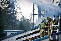JEROME A. POLLOS/Press..Kootenai County firefighters lower a fire hose from the roof of a home in Post Falls after extinguishing flames in an attic space Monday. No injuries were reported in the fire that is still under investigation.