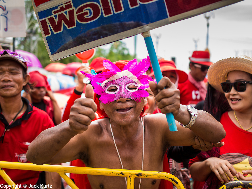 17 MAY 2014 - BANGKOK, THAILAND: A man wearing a carnival style mask at a Red Shirts rally on Aksa Road in Bangkok. Thousands of Thai Red Shirts, members of the United Front for Democracy Against Dictatorship (UDD), members of the ruling Pheu Thai party and supporters of the government of ousted Prime Minister Yingluck Shinawatra are rallying on Aksa Road in the Bangkok suburbs. The government was ousted by a court ruling earlier in the week that deposed Yingluck because the judges said she acted unconstitutionally in a personnel matter early in her administration. Thailand now has no functioning government. Red Shirt leaders said at the rally Saturday that any attempt to impose an unelected government on Thailand could spark a civil war. This is the third consecutive popularly elected UDD supported government ousted by the courts in less than 10 years.    PHOTO BY JACK KURTZ