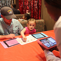 Jaselyn Martin, 3, of Nettleton, sits with her dad, Jason, as she gives her order to Chick-fil-a waitress Latavia Evans at the Daddy Daughter Dinner Tuesday night in Tupelo. The two have been coming to the event for the last three years.