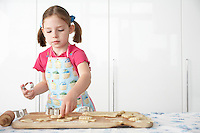Girl (5-6) cutting dough on board in kitchen