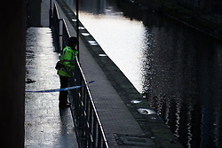 © Licensed to London News Pictures . 29/12/2013 . Manchester , UK . A PCSO looks in to the River Medlock off Oxford Road in Manchester City Centre . The search for 17 year old Adam Pickup from Stockport , who was last seen in the early hours of Saturday 28th December in Manchester City Centre following a night out with friends as , this evening (Sunday 29th December 2013), Greater Manchester Police say they have arrested two men in connection with the teenager's disappearance . Photo credit : Joel Goodman/LNP