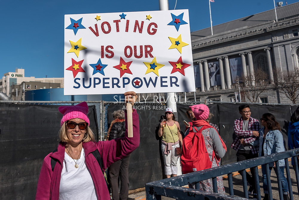 San Francisco, California, USA. 20th January, 2018. The 2018 Women's March in San Francisco, organized by Women's March Bay Area. A woman in a pink pussy hat holds a sign saying Voiting is Our Superpower at Civic Center Plaza.