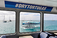 View of a seaplane through highspeed ferry window with #DryTortugas hashtag on a sign above. Both boat and airplane service can transport tourists to Dry Tortugas National Park from Key West, Florida.