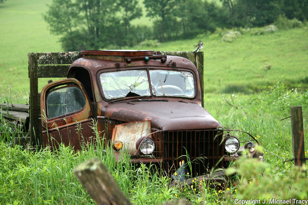 A vintage flatbed truck in a field in Upstate New York, quietly rusting away.
