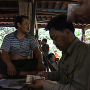 Cambodia, 2014. After being caught, poachers pay the fine in cash.