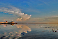 Breathtaking view at dawn across the ocean to Agung with pretty pagodas in the middleground. Bali, Indonesia.