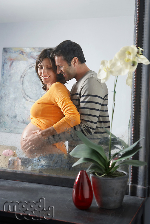Reflection in mirror of man embracing pregnant woman from behind in bedroom