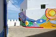 Street art murals painted on the walls and architecture inside the seaside town during the International Cultural Festival, Asilah, Northern Morocco, 2015-08-11.<br /><br />Asilah is a sleepy fishing town in the North of Morocco, just one hour south of Tangier. While not completely off Morocco's well-beaten path, it's often missed by travellers bound inland for Fez or Chefchaouen, yet has a uniquely alluring charm. With an immaculately restored medina that's re-painted vivid shades of blue & white each summer, Asilah has the feel of being Morocco's own Santorini - a great spot to see the more chilled out, seaside town life in Morocco.  <br /><br />Asilah is synonymous with art and the peaceful seaside town is home to over 50 resident artists. It is packed full of art galleries, studios and exhibition spaces with artists from around the country selling their work. Each summer, the town invites artists from across the globe to visit and take part in an annual arts festival. The festival begins in July and commences by the artists and locals re-painting the medina. They purposefully leave large spaces of the medina walls white-washed blank, ready for artists to create and design new murals and street art during the festival. Artwork can be found everywhere, including sketches and engravings etched onto doorways and walls by children. Large sections are even allocated for children to paint their own ideas and fun workshops are held encouraging children to work together and help paint new murals onto the walls. This is actually how Asilah began its synonymous relationship with art. In 1978 seven Moroccan artists were invited to the town to hold art classes for children, inviting them to draw on the walls of the medina. The festival goes on for a number of weeks showcasing a range of artistic disciplines, from music and poetry to performance and painting, and everything inbetween. Its mark is left on the town for the remainder of the year, as the murals and artwork are le