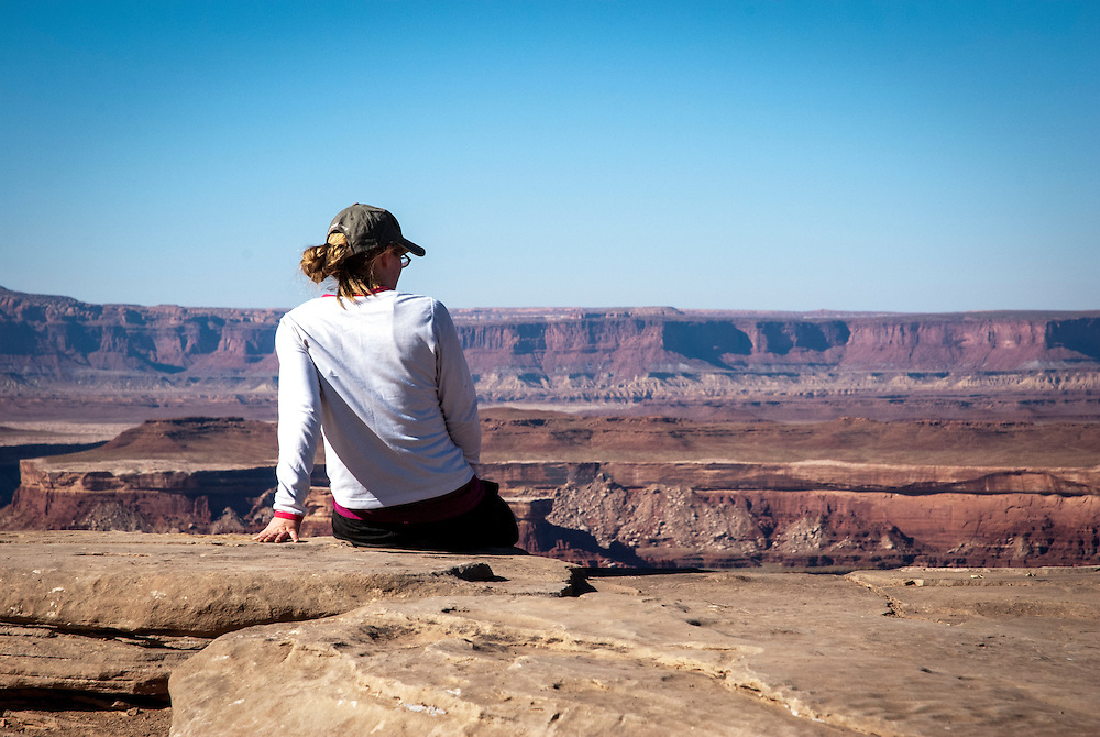 A young woman takes in the expansive views into the canyon on while touring the White Rim Trail near Moab, Utah.