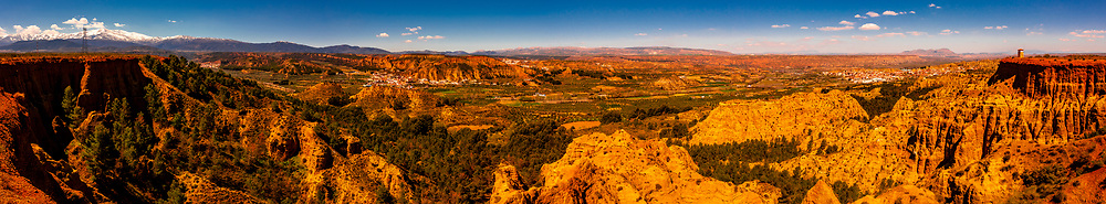 Panoramic view of Badlands from Mirador del Fin del Mundo (the towns of Purullena-far left, Los Banos-above, center and Purullena-far right), near Guadix, Granada Province, Andalusia, Spain.