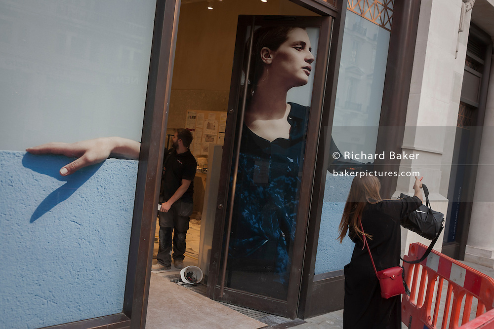 A woman searches for an item beneath a retail poster in central London.