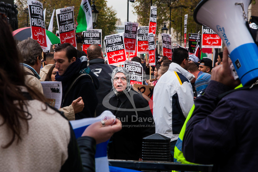 Downing Street, London, November 15th 2014. Dozens of Palestinians and their supporters faced a small group of Israeli counter protesters as they demonstrated outside the gates of Downing Street against Israel. Police had to intervene as several from both sides took exception to what was being said, with the half-dozen-strong Israeli group eventually moving off. Pictured: A palestinian supporter, centre, exchanges views with a handful of pro-Israel counter-protesters.