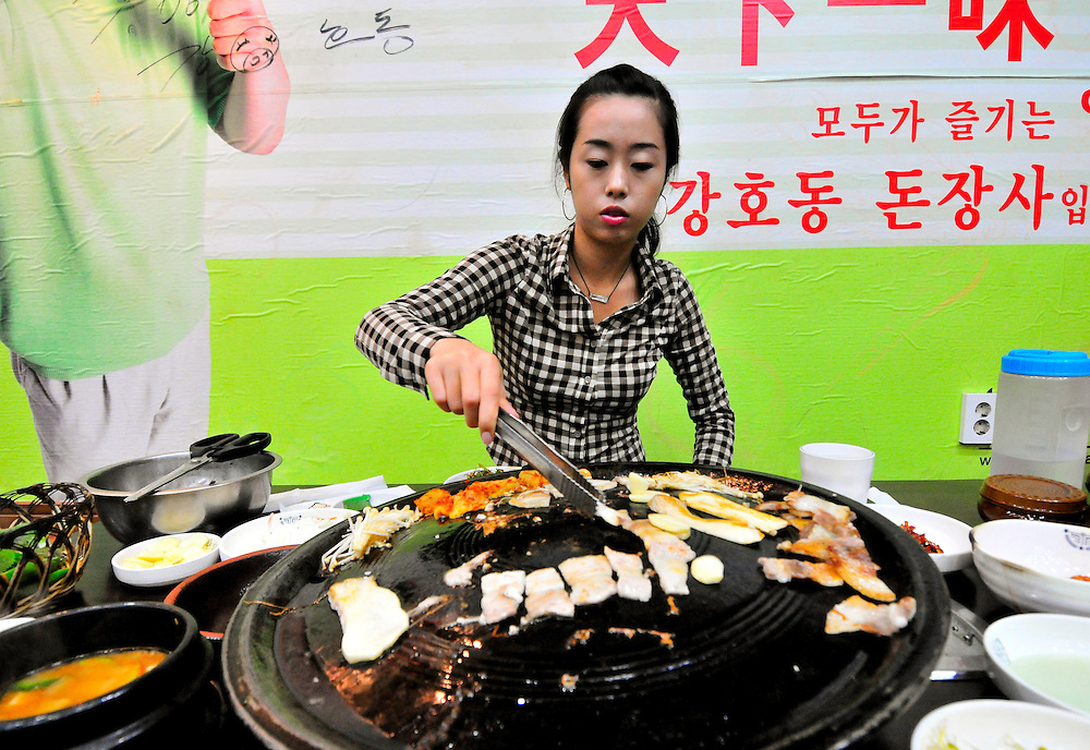 A young Korean woman cooks pork during a meal in Busan, Korea. Samgyupsal is a traditional Korean meal of grilled pork.