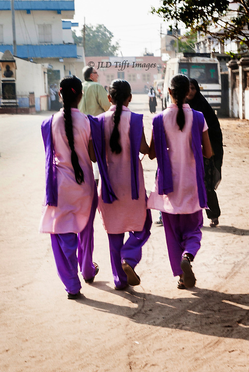 Seen from the back, long hair neatly braided, wearing pink and purple school uniform of shalwar and kameez.