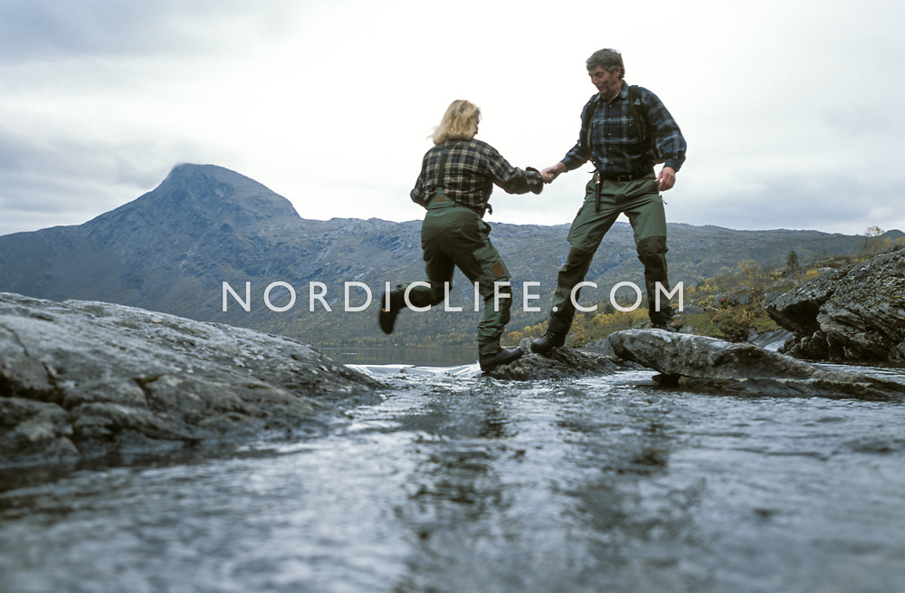Woman passing brook, man giving a helping hand.<br />