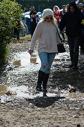 © Licensed to London News Pictures. 13/06/2015. Isle of Wight, UK.  Festival goers battle through muddy conditions at Isle of Wight Festival 2015 on the morning of Saturday Day 3.  Yesterday suffered torrential rain all afternoon and evening, after a first day of warm sun.  This years festival include headline artists the Prodigy, Blur and Fleetwood Mac.  Photo credit : Richard Isaac/LNP