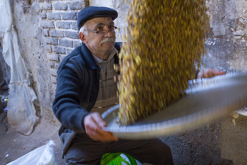 A pistachio nut seller at work in the old bazaar (Tabriz, Iran, 2012).