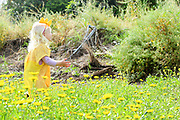 Young blond girl of four plays outdoors in an uncultivated field