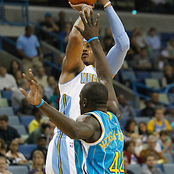 October 29, 2010; New Orleans, LA, USA; Denver Nuggets small forward Carmelo Anthony (15) shoots over New Orleans Hornets center Pops Mensah-Bonsu (44) during the first half at the New Orleans Arena.  Mandatory Credit: Derick E. Hingle..